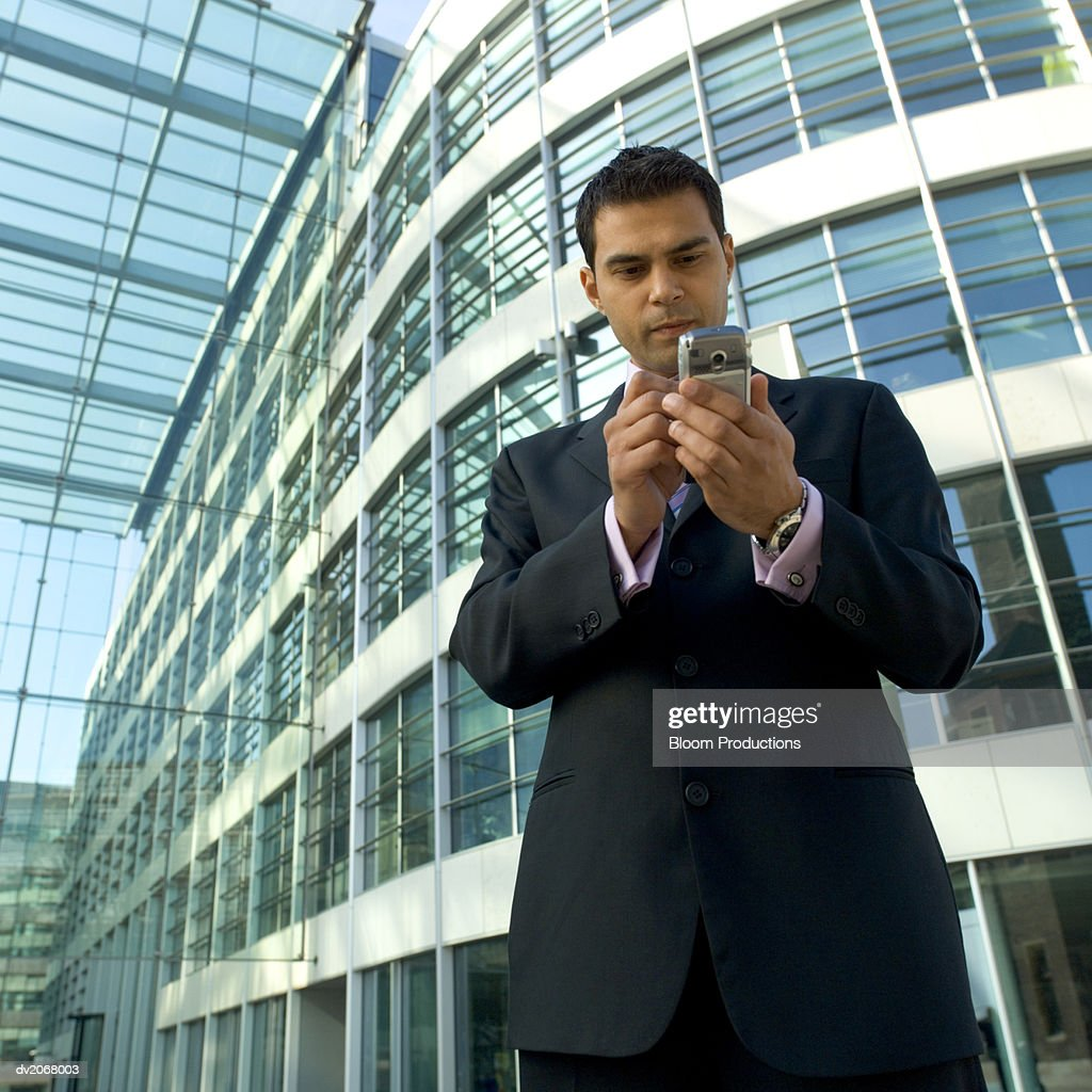 Businessman Standing Outside a Glass Building, Using a Handheld PC : Stock Photo