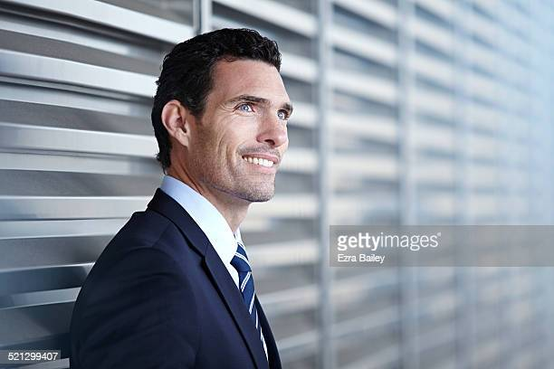 A businessman standing outside a modern office.