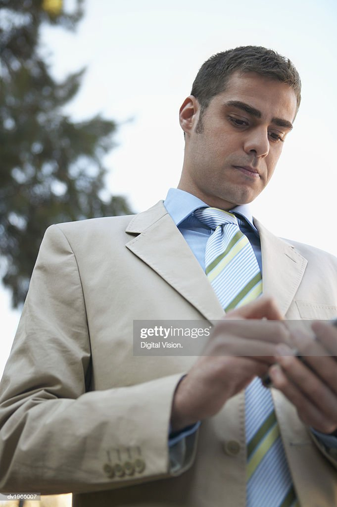 Businessman Standing Outside Using His Handheld PC : Stock Photo