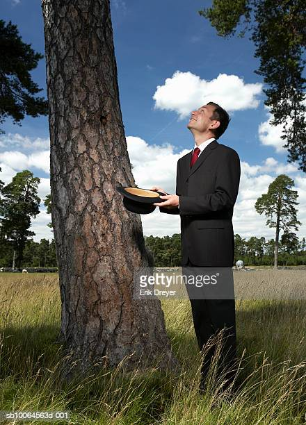 Businessman standing under tree holding hat, looking up, side view