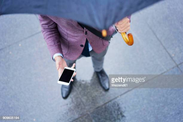 Businessman standing under umbrella holding cell phone, partial view