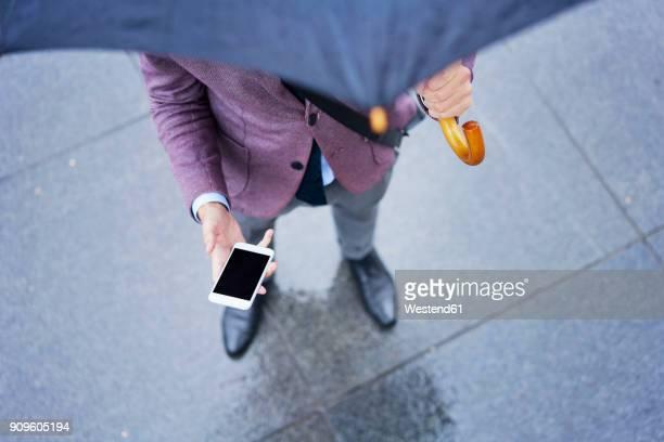 businessman standing under umbrella holding cell phone, partial view - onderste deel stockfoto's en -beelden