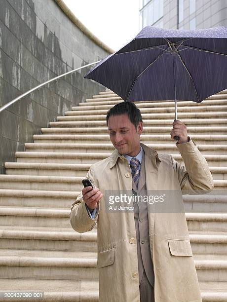 Businessman standing under umbrella in rain, using mobile phone