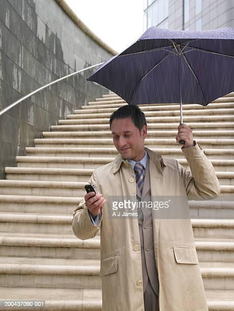 ビジネスマンのパラソルの下で、独立したレイン、携帯電話を使用する
