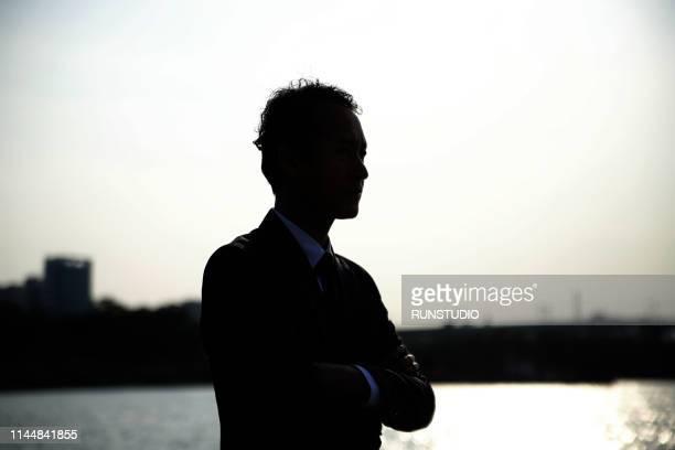 businessman standing with arms folded at sunset - kontur stock-fotos und bilder