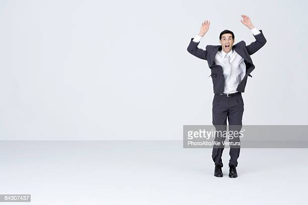Businessman standing with arms up, mouth and eyes wide open