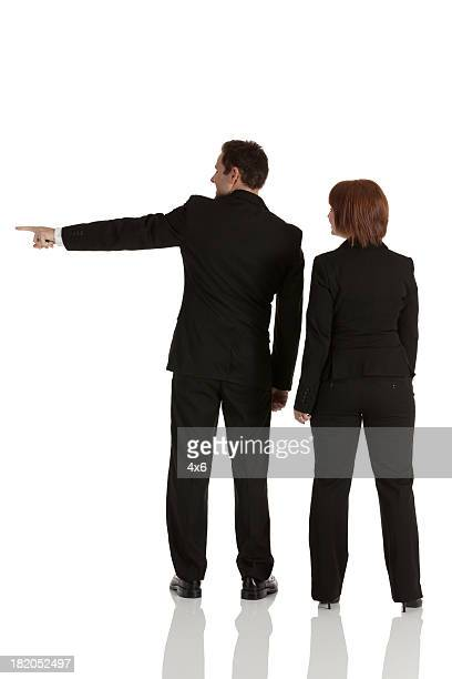 Businessman standing with businesswoman and pointing sideways