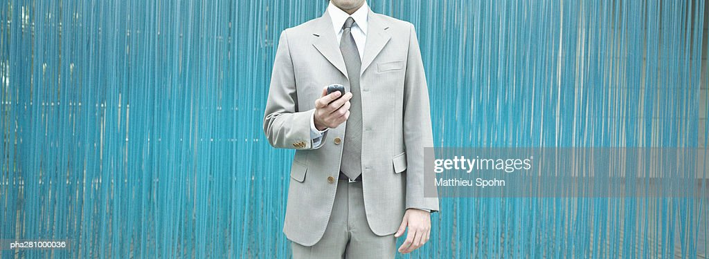 Businessman standing with cell phone in hand, mid-section, panoramic : Stockfoto