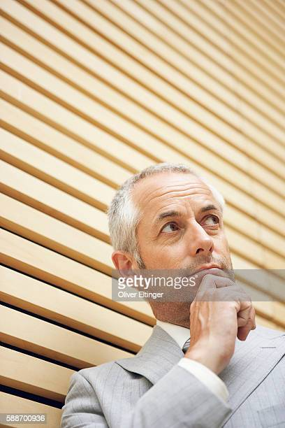 businessman standing with hand on chin - oliver eltinger stock-fotos und bilder