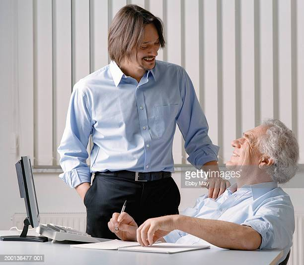 Businessman standing with hand on seated man's shoulder in office