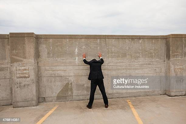 Businessman standing with hands against wall
