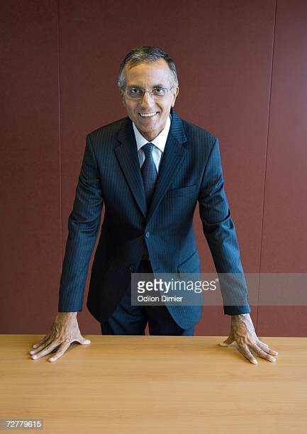 Businessman standing with hands on table, portrait