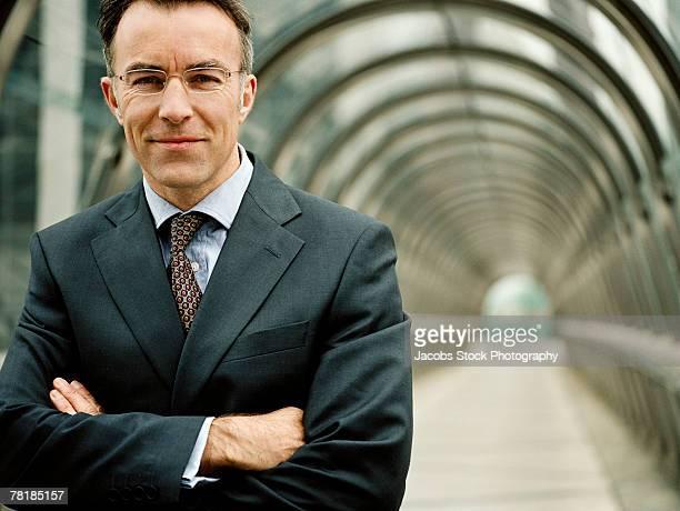 businessman standing with his arms folded - bogen architektonisches detail stock-fotos und bilder