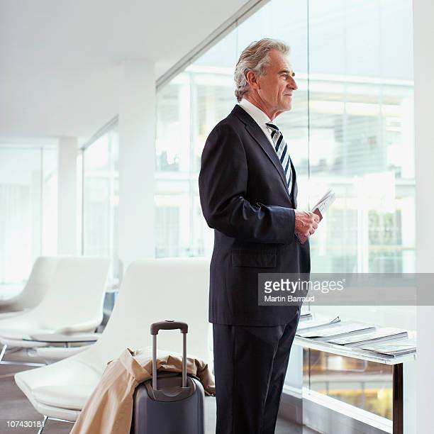Businessman standing with passport and luggage in airport