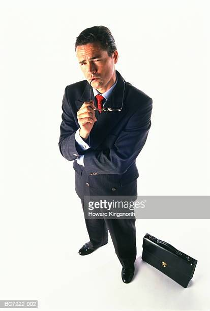 Businessman standing with pensive expression, elevated view