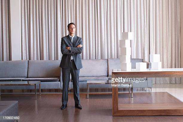 Businessman standing with stack of cubes in hotel lobby