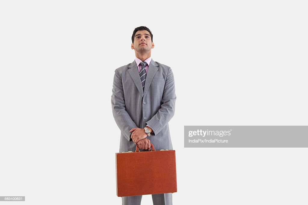 Businessman standing with suitcase : Stock Photo