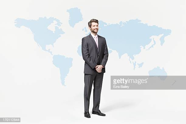 Businessman standing with world map.