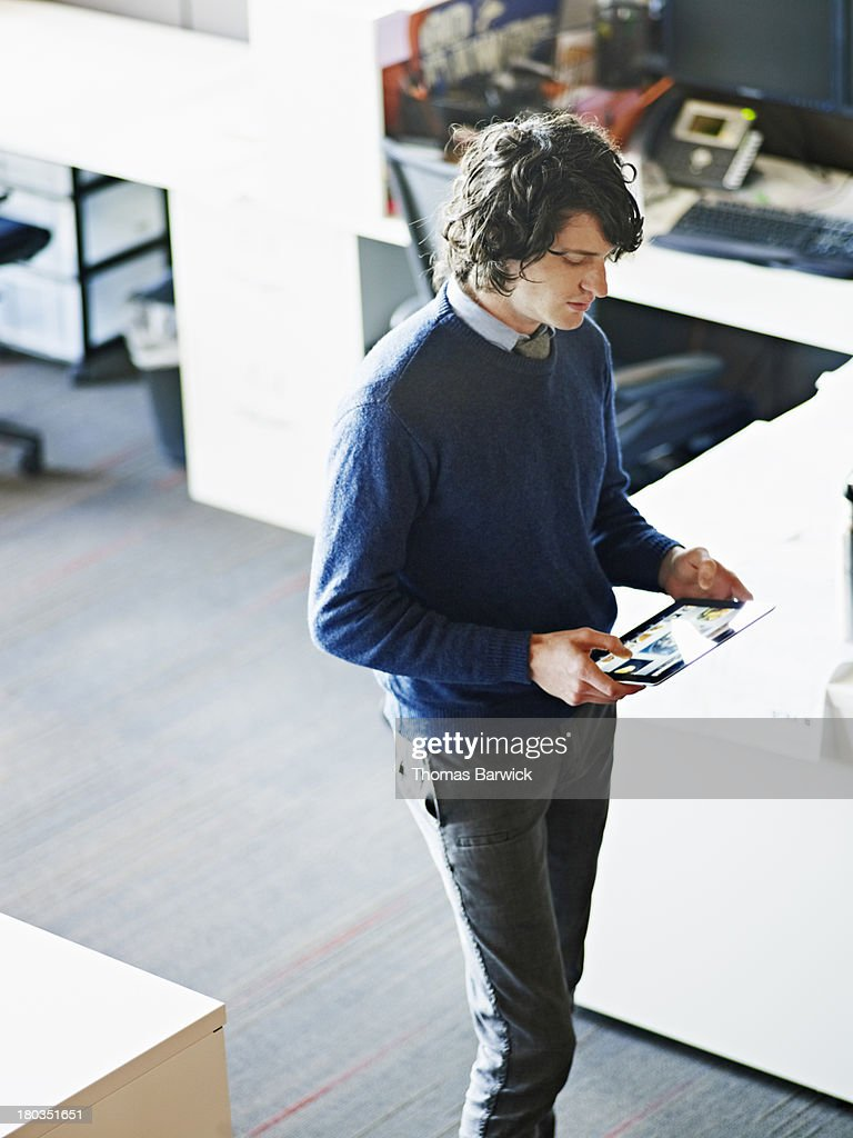 Businessman standing working on digital tablet : Stock Photo