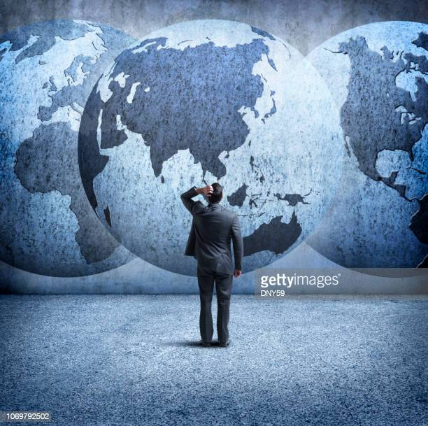 businessman stands and looks up at three interlocking globes on wall - international politics stock pictures, royalty-free photos & images