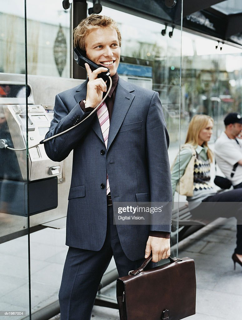 Businessman Stands by a Bus Stop Talking on a Payphone : Stock Photo