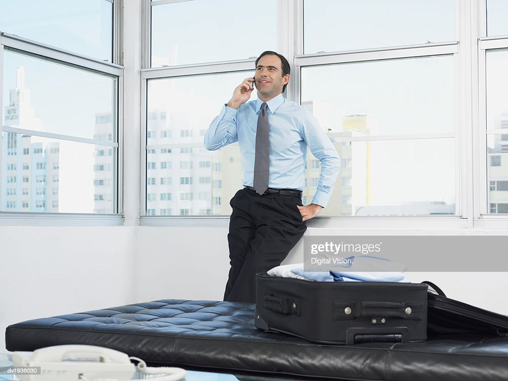 Businessman Stands by a Window in a Hotel Room Talking on His Mobile Phone : Stock Photo