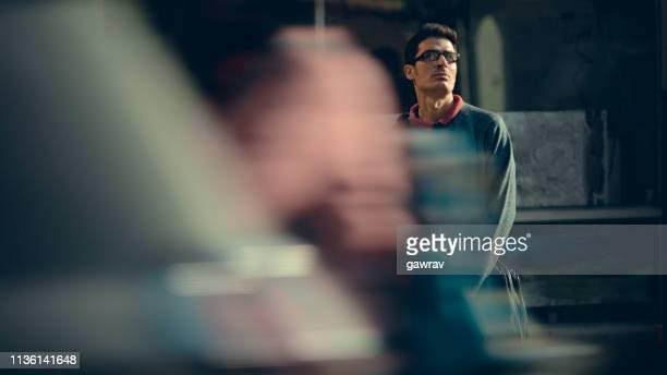 businessman stands by fast paced city road. - foco diferencial imagens e fotografias de stock