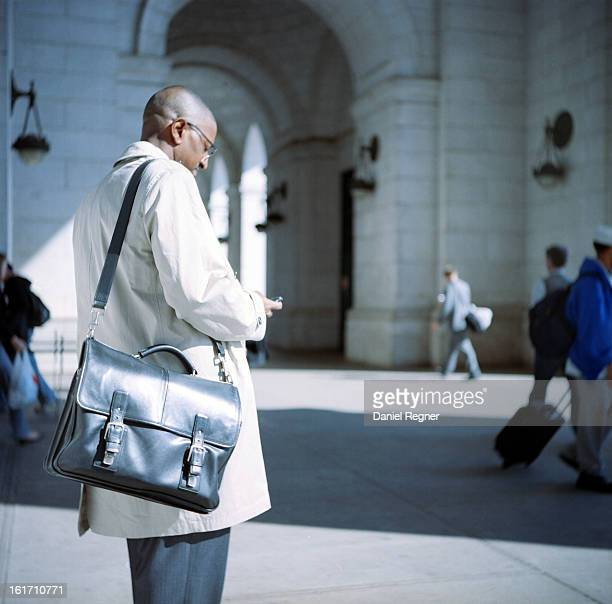 CONTENT] A businessman stands in Washington DC conducting business on his smartphone Showing an average working class citizen with a black briefcase