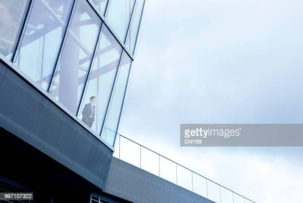 businessman stands inside building and looks out through window - looking through window stock pictures, royalty-free photos & images