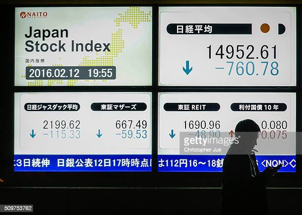 A businessman stands next to a stock market indicator board on February 12 2016 in Tokyo Japan The Nikkei Stock Average finished 11% down for the...