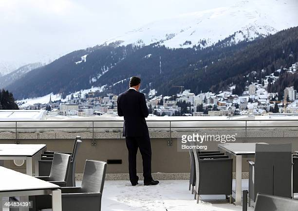 A businessman stands on a snow covered outdoor terrace at the InterContinental hotel operated by InterContinental Hotels Group Plc in Davos...
