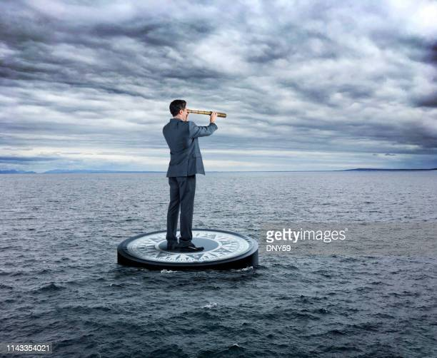businessman stands on compass looking through spyglass in stormy seas - morality stock pictures, royalty-free photos & images