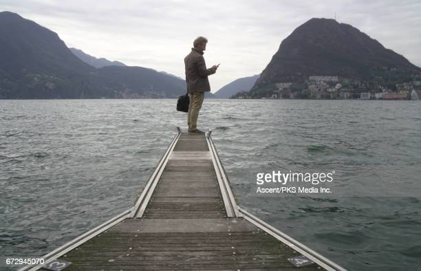 Businessman stands on lake pier, sends text