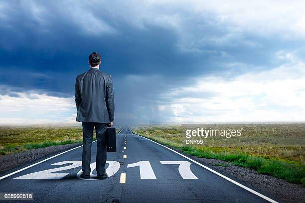 businessman stands on long road with 2017 painted on it - 2017 fotografías e imágenes de stock