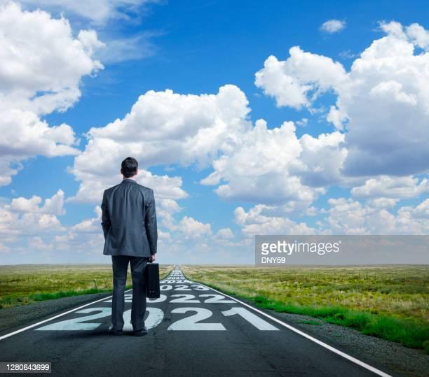 ビジネスマンは、その上に描かれた2021とその後の年で長い道のりに立っています - anticipation ストックフォトと画像