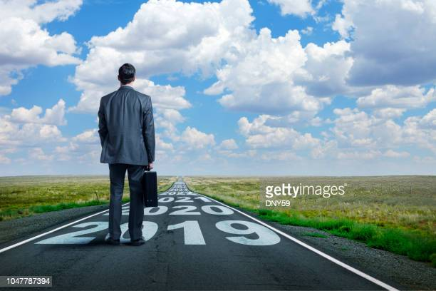 businessman stands on long road with series of years painted on it - calculating stock pictures, royalty-free photos & images