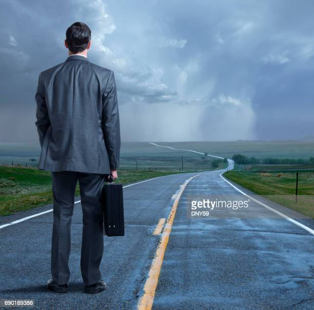 Businessman Stands On Long Winding Road In The Rain
