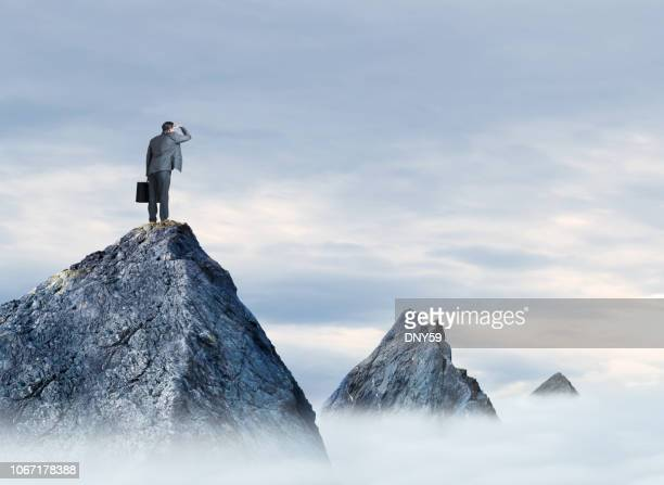 businessman stands on mountain peak looking at two peaks in the distance - distant stock pictures, royalty-free photos & images