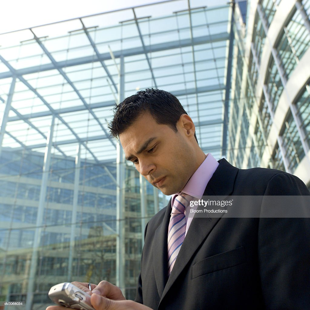 Businessman Stands Outside a Glass Building Using a Handheld PC : Stock Photo