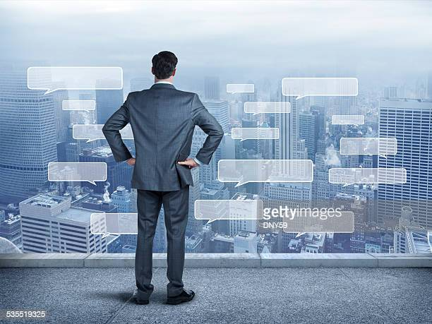 Businessman staring at a large city full of text bubbles