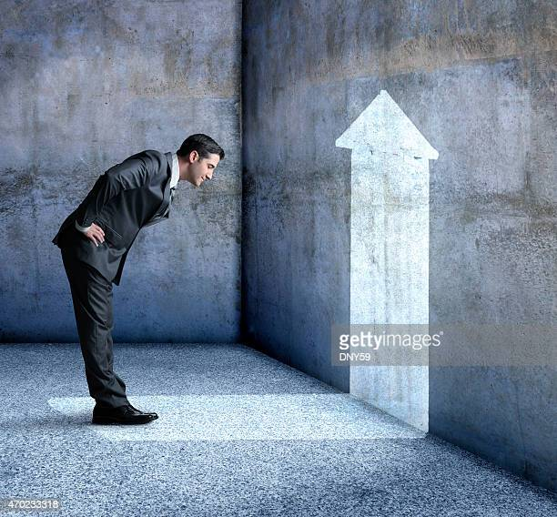 businessman staring at an arrow projected on a wall - bending over stock pictures, royalty-free photos & images