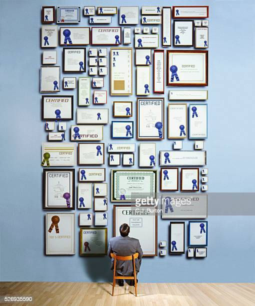 businessman staring at certificates on wall - diploma foto e immagini stock