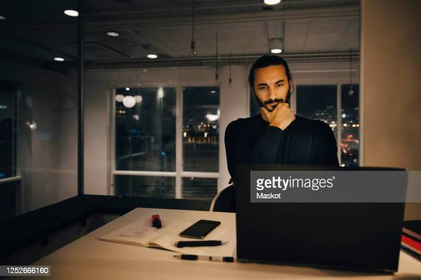 businessman staring at laptop while thinking in office - staring stock pictures, royalty-free photos & images