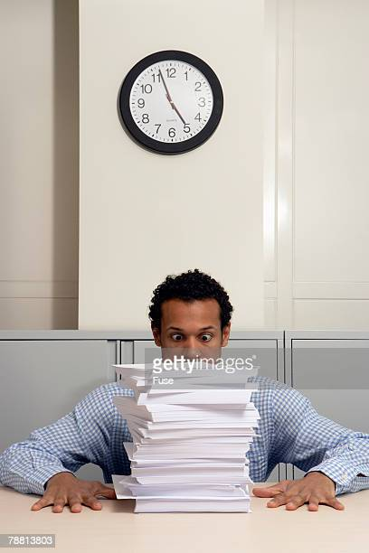 Businessman Staring at Stack of Paperwork
