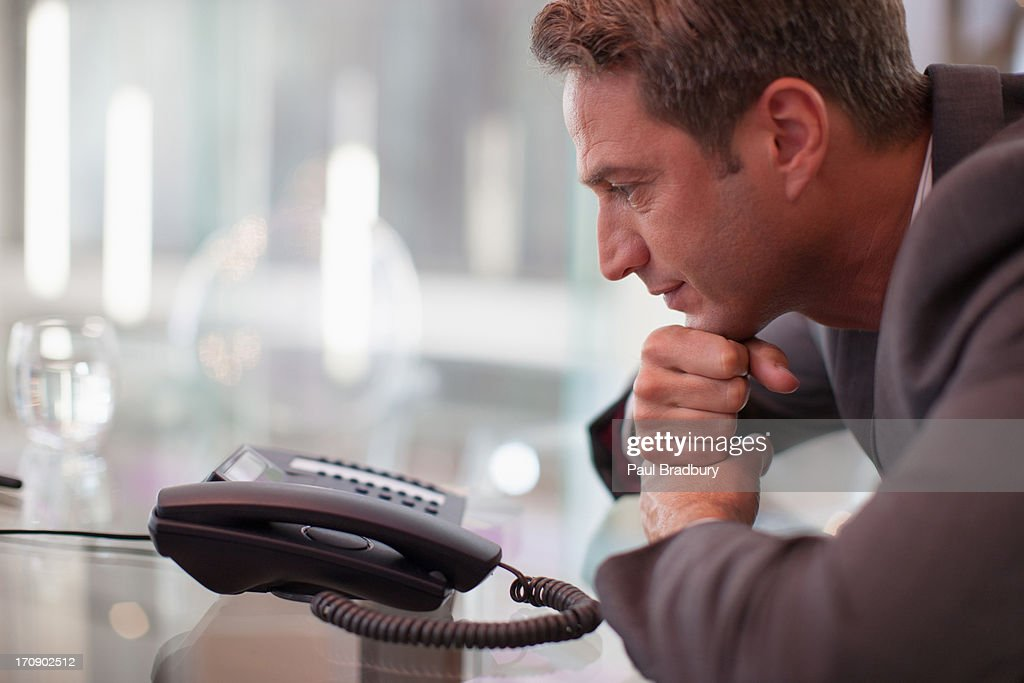 Businessman staring at telephone waiting for it to ring : Stock Photo