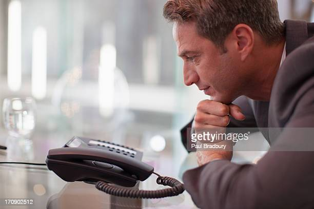 businessman staring at telephone waiting for it to ring - staring stock pictures, royalty-free photos & images