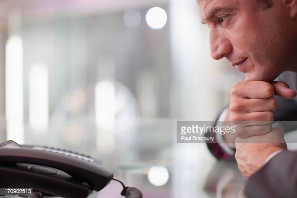 Un homme d'affaires regardant de téléphone à appeler en attente pour