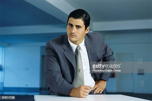 Businessman staring intently at camera with clenched fist on table