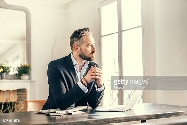 businessman staring out of the window with a pensive expression - illustrator stock photos and pictures