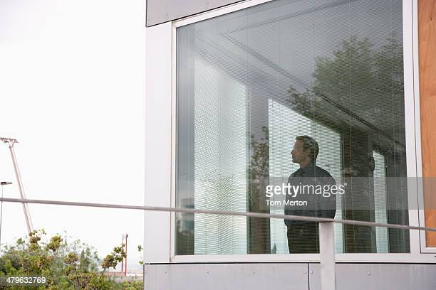 businessman staring out office window - lingering stock pictures, royalty-free photos & images